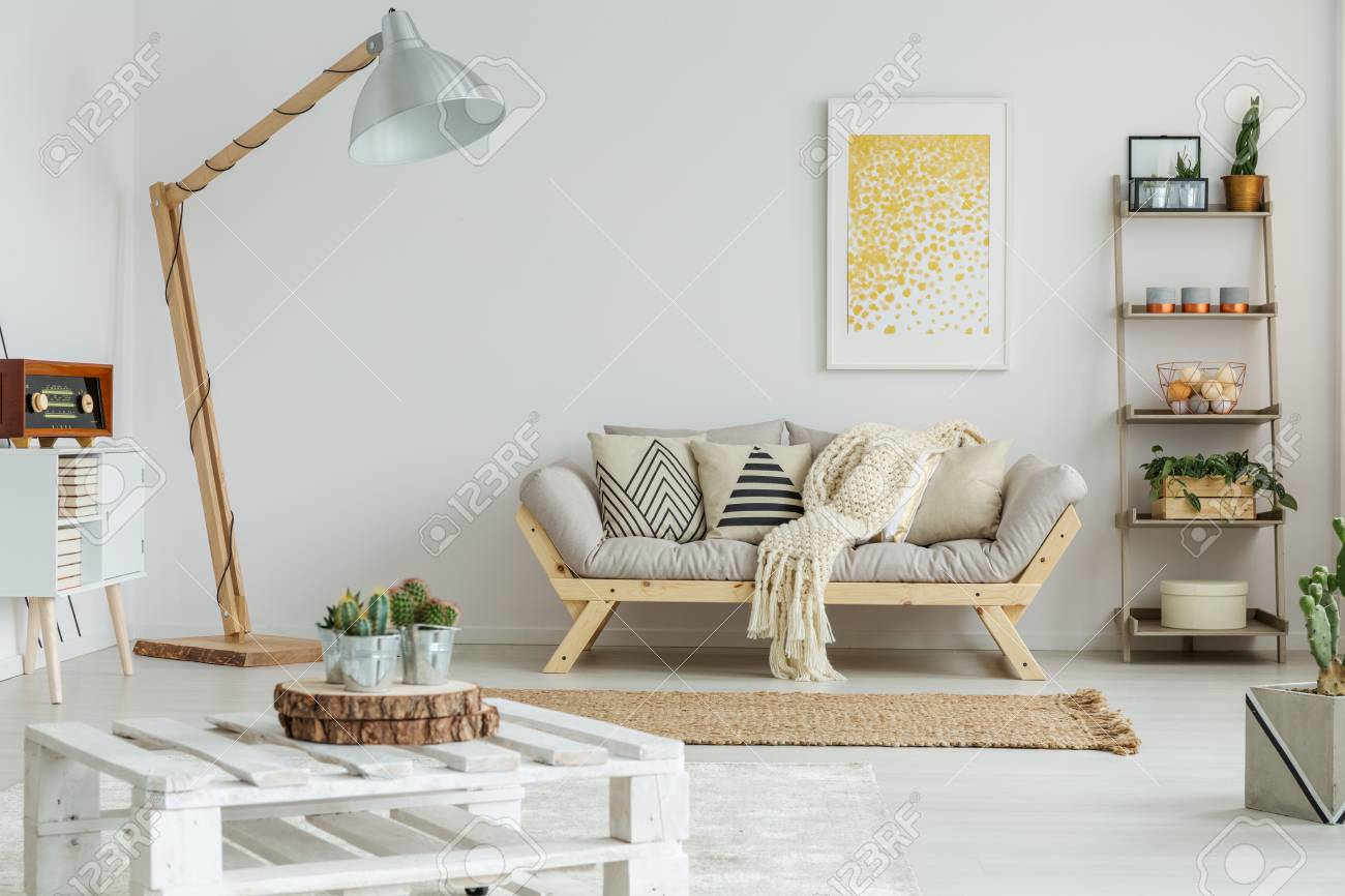 Yellow Painting Hangs Over Grey Sofa In Decorative Living Room Stock ...