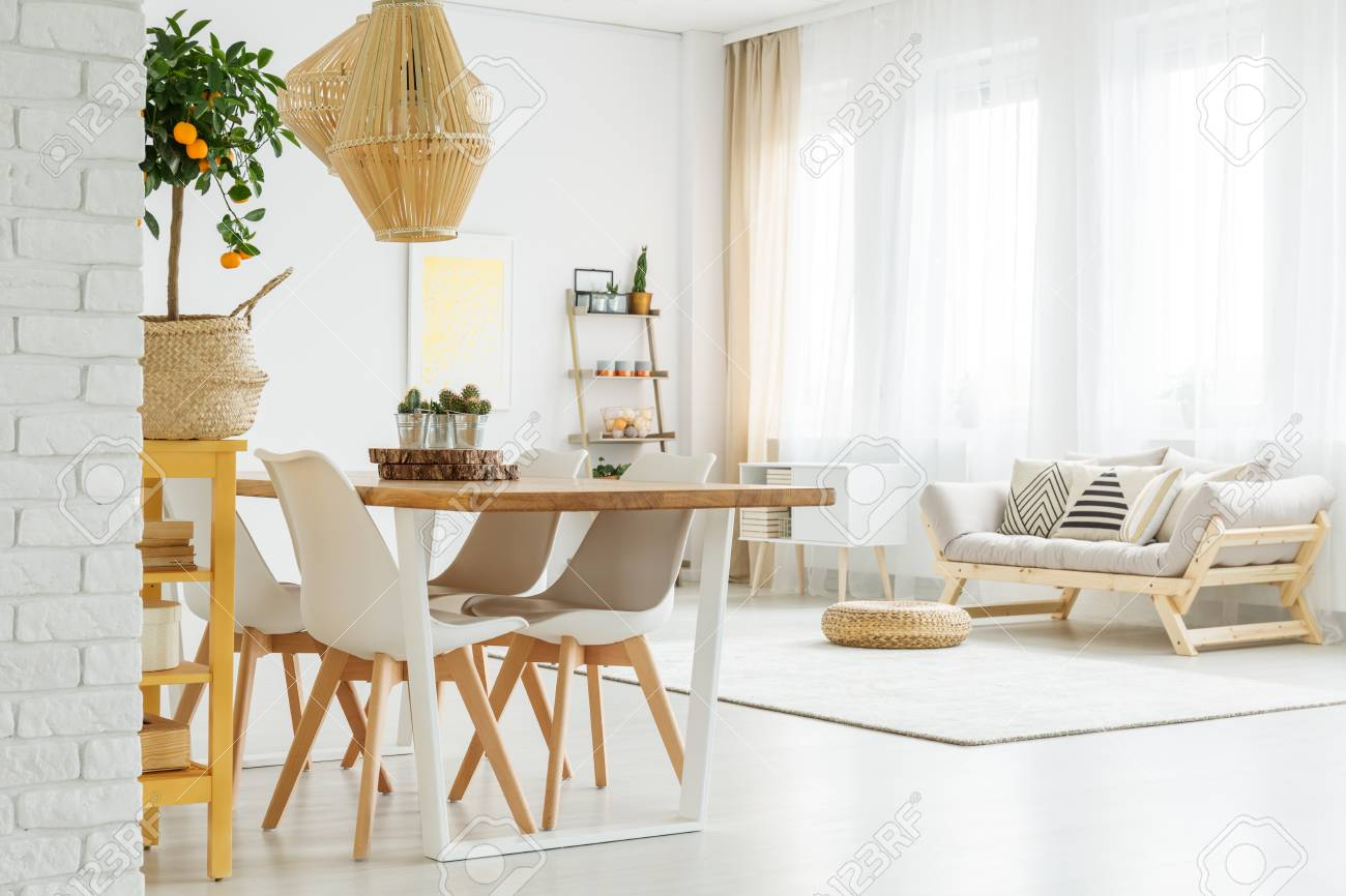 Espacio abierto con mesa de comedor, sillas blancas y un cómodo sofá gris