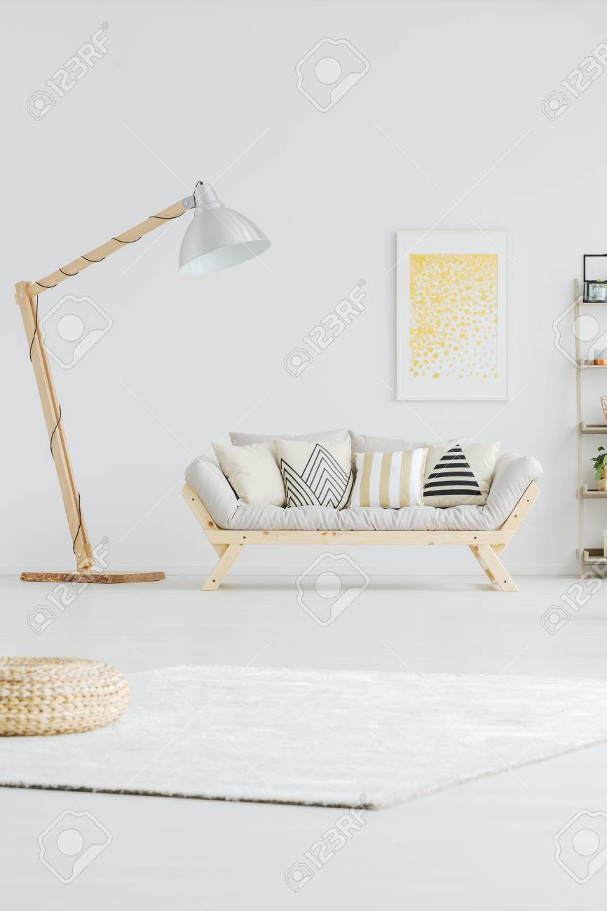 Designed Big Lamp Next To Grey Sofa And Yellow Painting On Wall