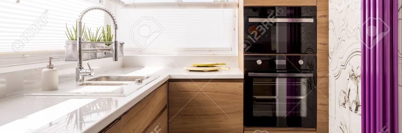 Cocina Diseñada Con Encimera Blanca Brillante Y Grifería De Acero