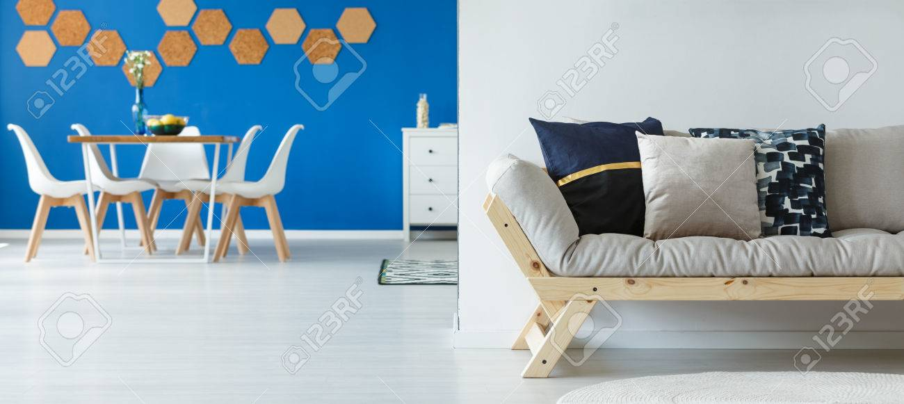 Flores en florero de vidrio en la pequeña mesa de comedor con sillas  blancas en la habitación espaciosa con pared azul
