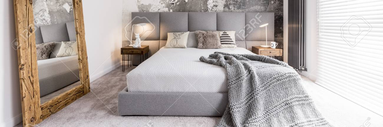 Big Mirror In Wooden Frame In Grey Cozy Bedroom With King Size Bed Stock  Photo
