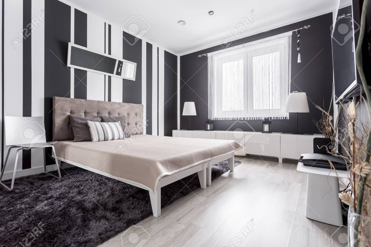 Luxurious Modern Bedroom With Striped Wallpaper And Bed With Stock