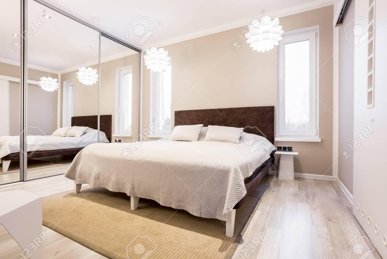 Chambre beige tonique avec armoire à glace et lit simple