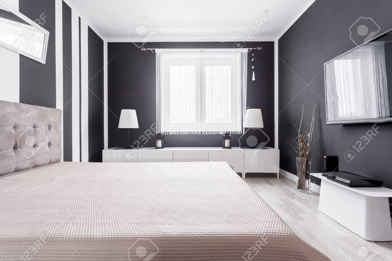 . Relax zone with bed  TV and gaming console in modern black bedroom
