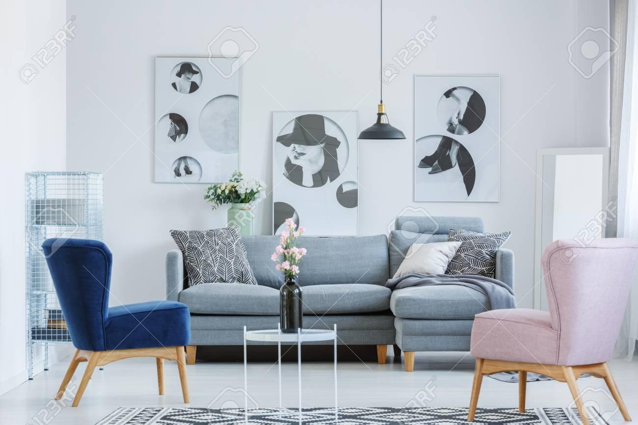 Fauteuils roses et bleus dans un salon confortable avec canapé gris et vase  noir sur petite table de café