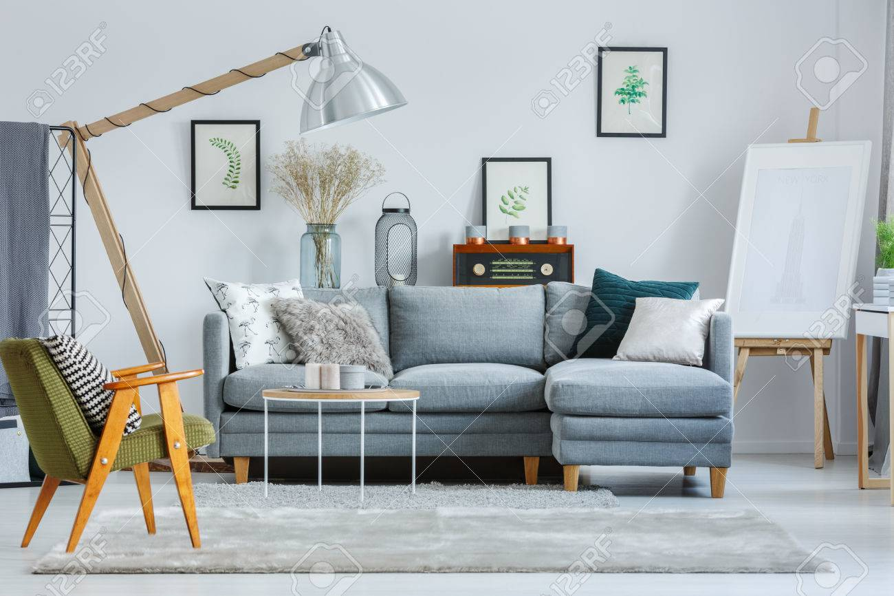 Classic Green Armchair In Living Room With Easel And Design Lamp Above Grey Sofa Pillows