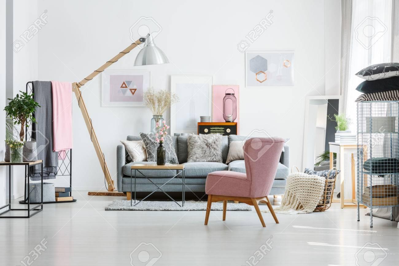 Canapé gris avec des oreillers décoratifs dans le salon avec fauteuil rose  et radio vintage