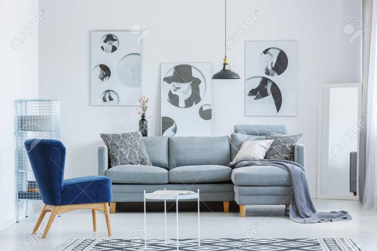 Fauteuil bleu dans le salon du concepteur avec des affiches simples et un  canapé gris avec des oreillers à motifs