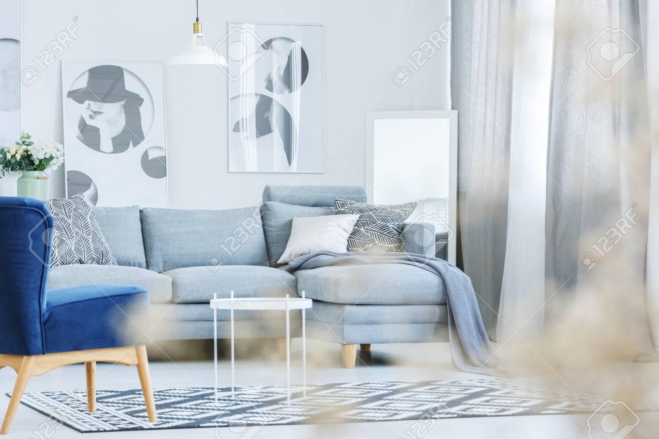 Fauteuil bleu dans le salon moderne avec des oreillers à motifs sur un  canapé gris contre le mur avec des affiches à la mode