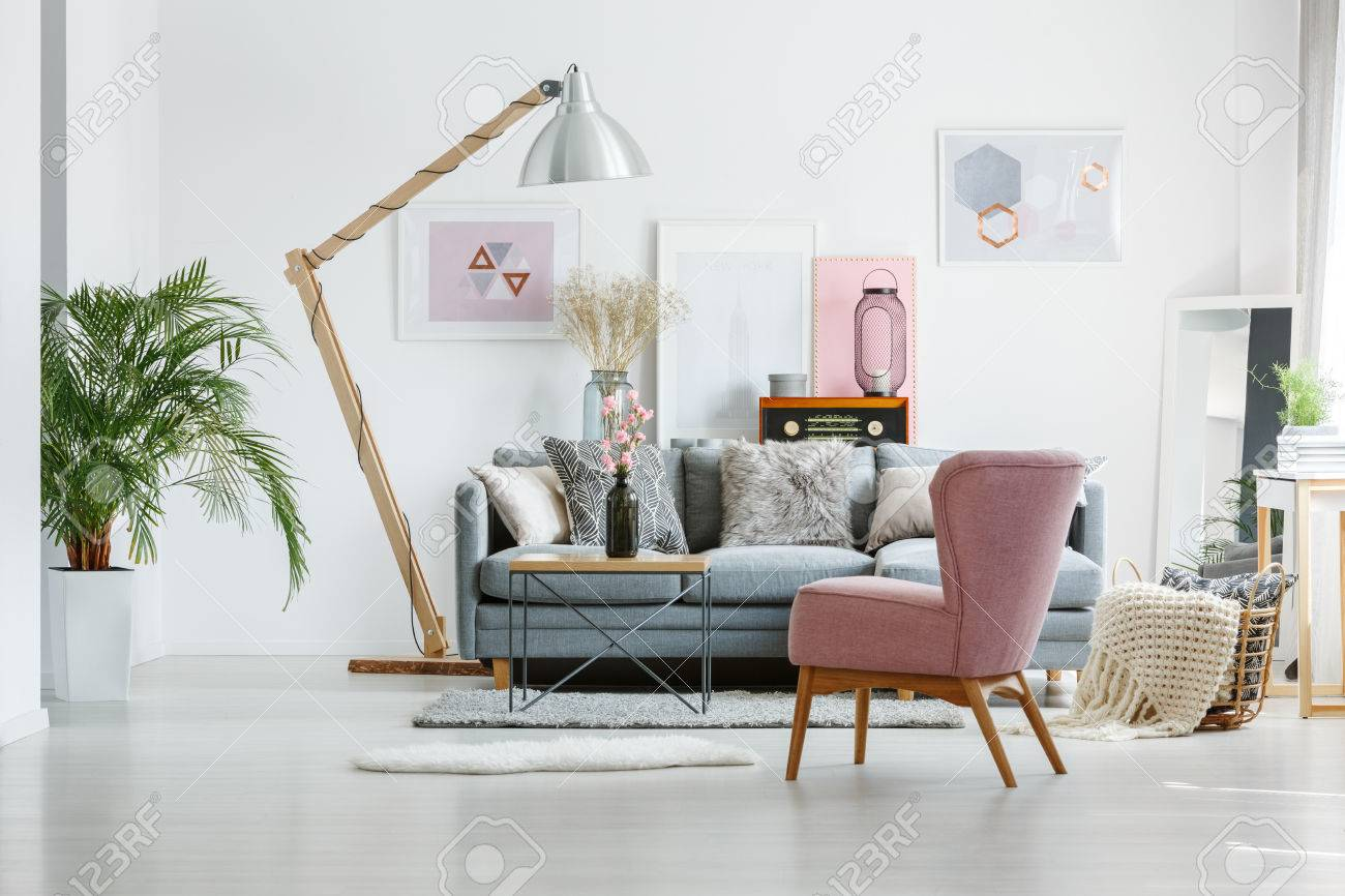 Beige Blanket In Basket On Floor In Living Room With Pink Armchair ...