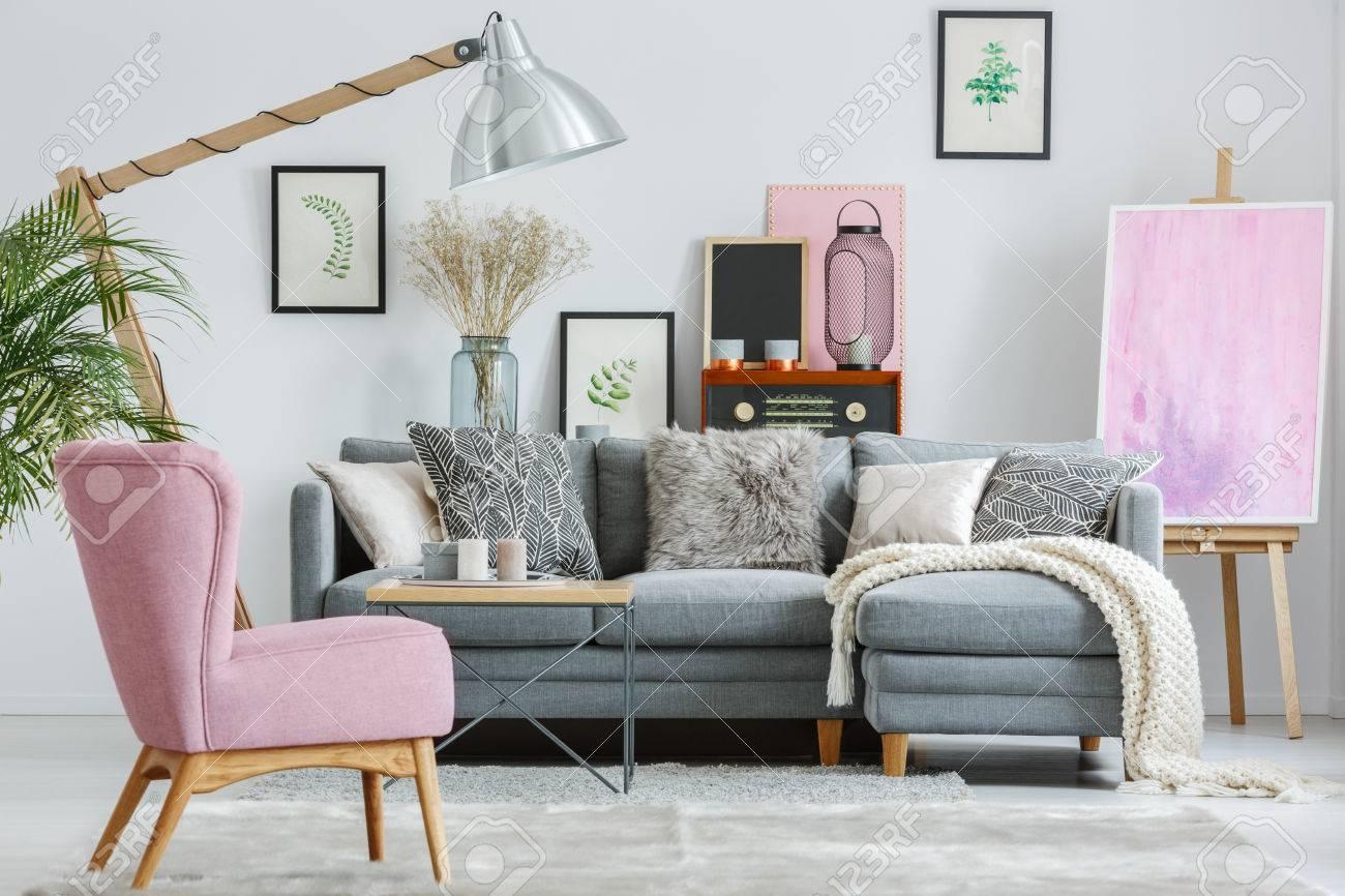 Fauteuil rose sur tapis gris dans le salon avec une couverture blanche sur  canapé gris et lampe design