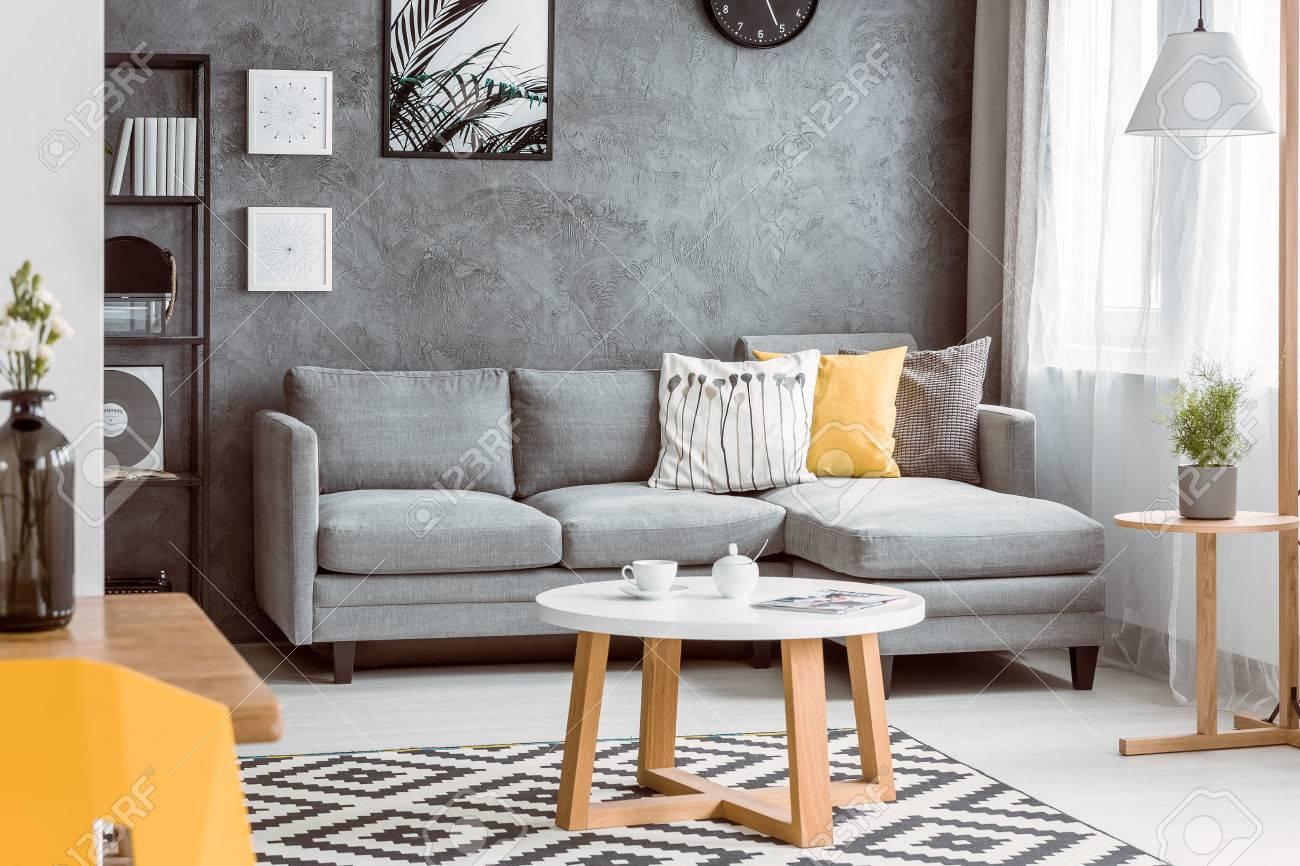 Table basse en bois sur un tapis noir et blanc dans le salon avec un  oreiller jaune sur canapé gris