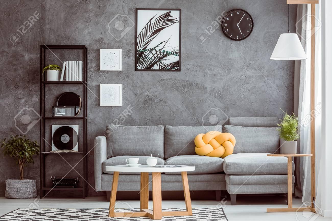 Schwarze Uhr Und Poster Auf Dunkler Wand Uber Grauem Sofa Mit Gelbem