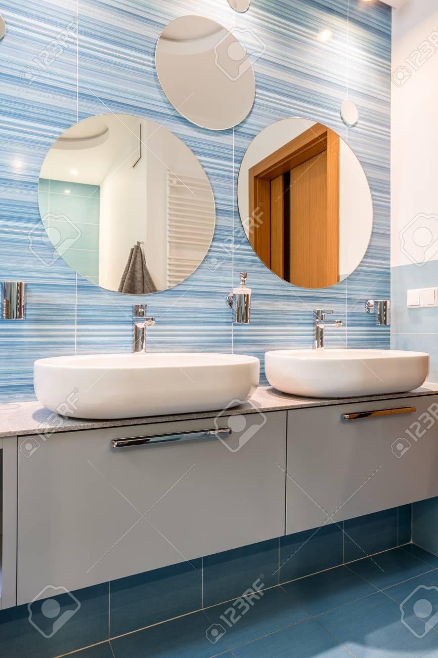 El Bano Azul.Dos Lavabos En Armarios Blancos Simples En El Bano Azul Moderno Con Espejos Redondos