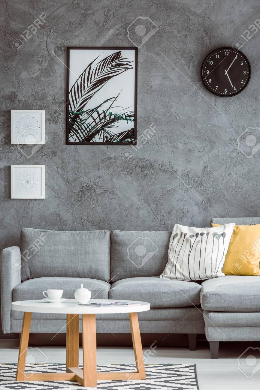 Salon simple avec des affiches et horloge noire sur le mur de béton  au-dessus du canapé gris avec oreiller jaune