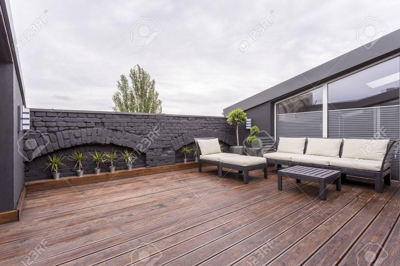 Plantas Y Muebles De Jardín De Color Beige En La Terraza Con Piso De Madera Y Pared De Ladrillo Negro