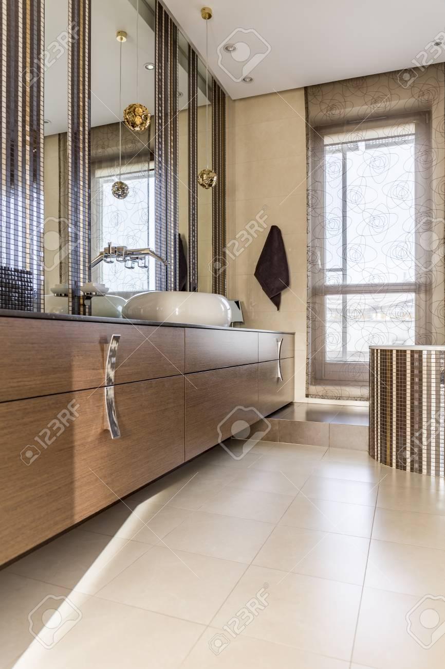 Moderno bagno colorato neutro con lampade decorative oro