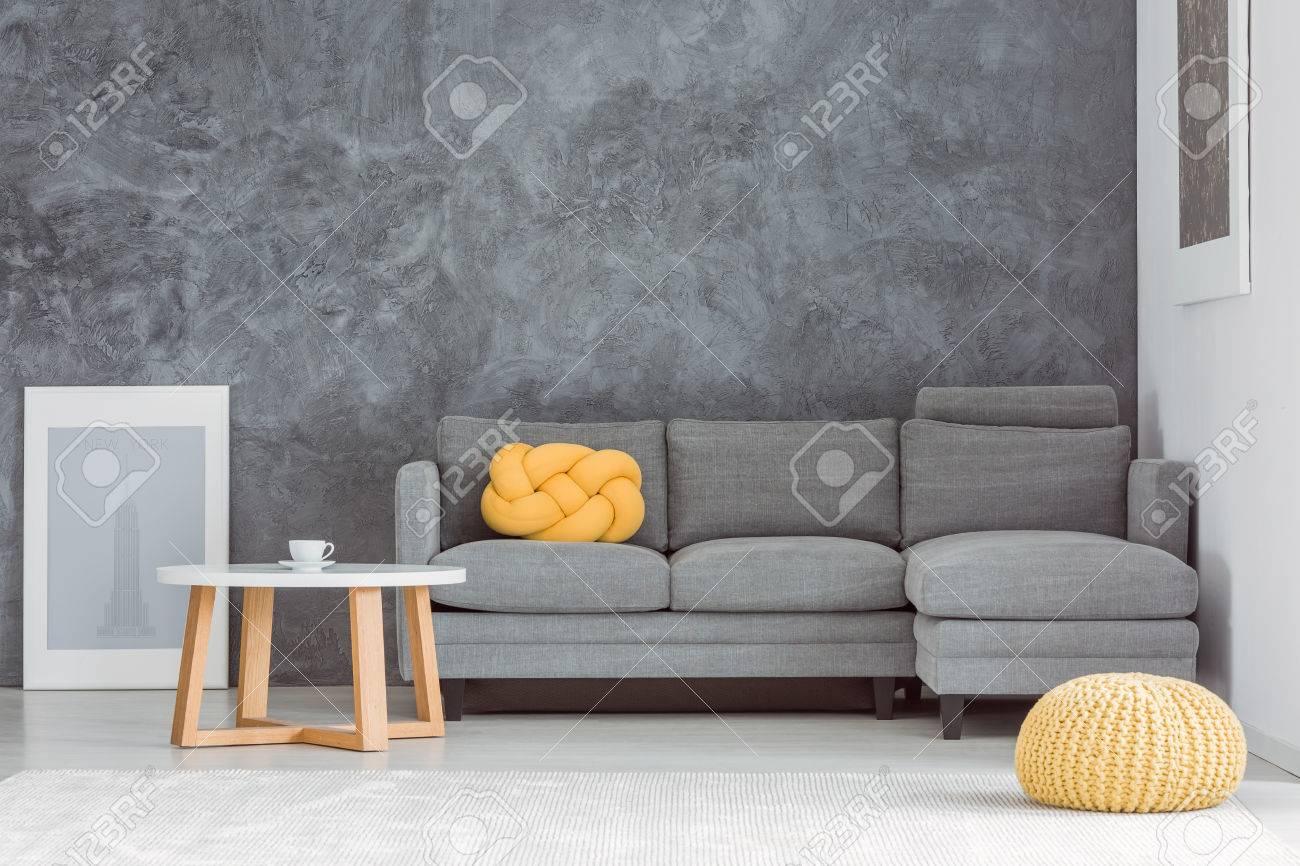 Pouf Jaune Devant Un Canape Gris Contre Mur En Beton Dans Le Salon