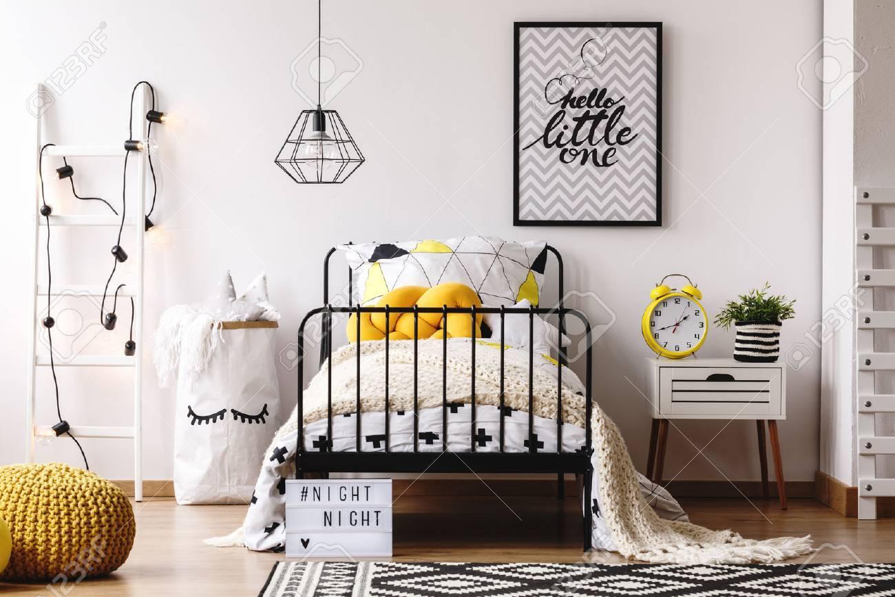 Rétro horloge jaune sur le chevet blanc dans la chambre d\'enfants créative  avec affiche sur le mur