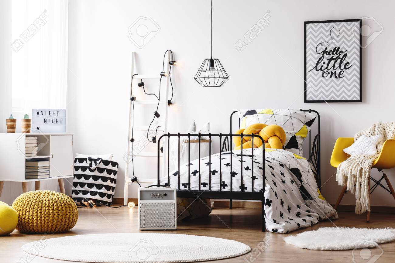 Blanket on yellow chair next to bed with yellow pillow in kids