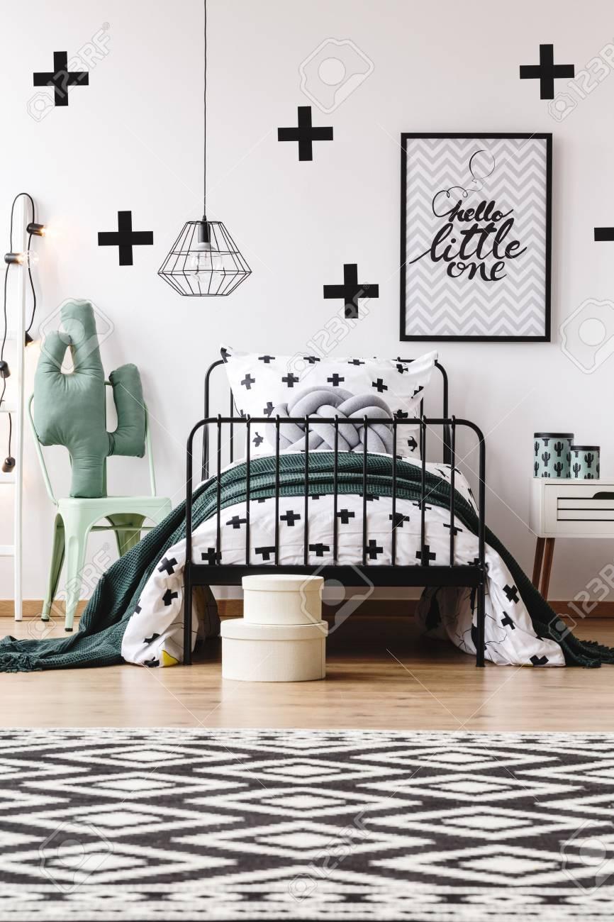 Tapis noir et blanc géométrique dans les chambres des enfants avec jouet  sur chaise à côté de lit avec oreiller gris