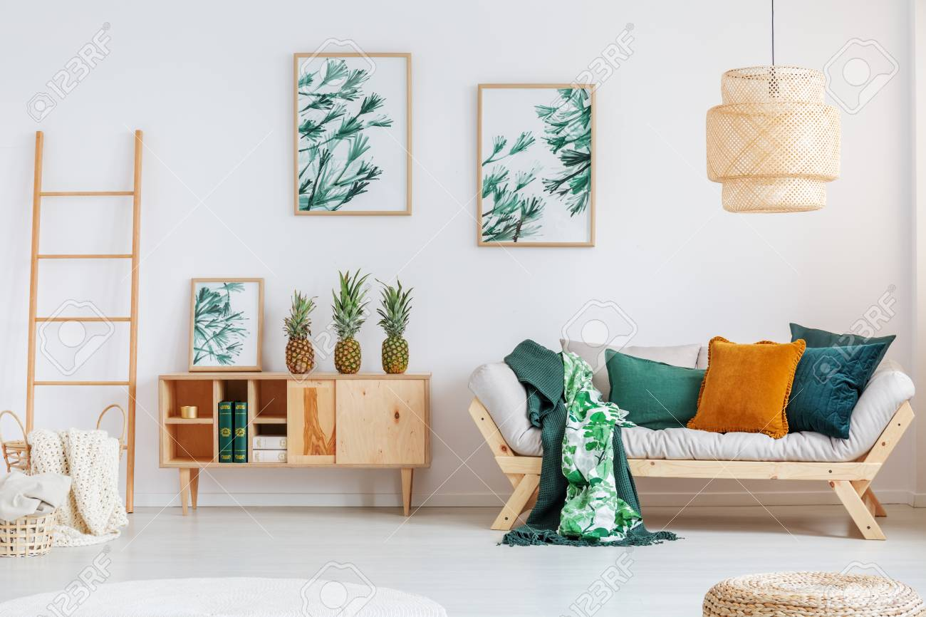 Pineapples on rustic cupboard between ladder and beige sofa with..