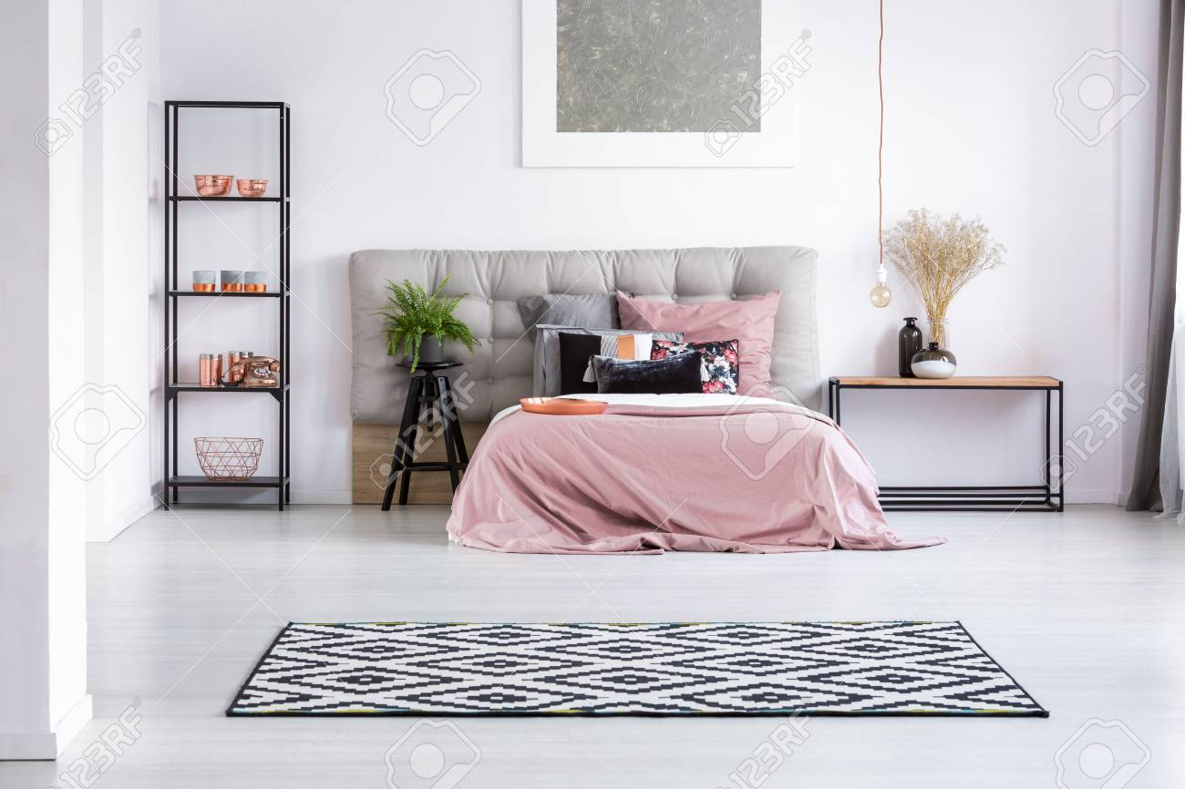 Black and white geometric carpet in bedroom with copper elements and king size bed with