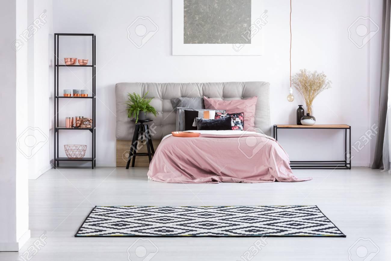 Tapis géométrique noir et blanc dans la chambre avec des éléments en cuivre  et un lit king-size avec superposition rose