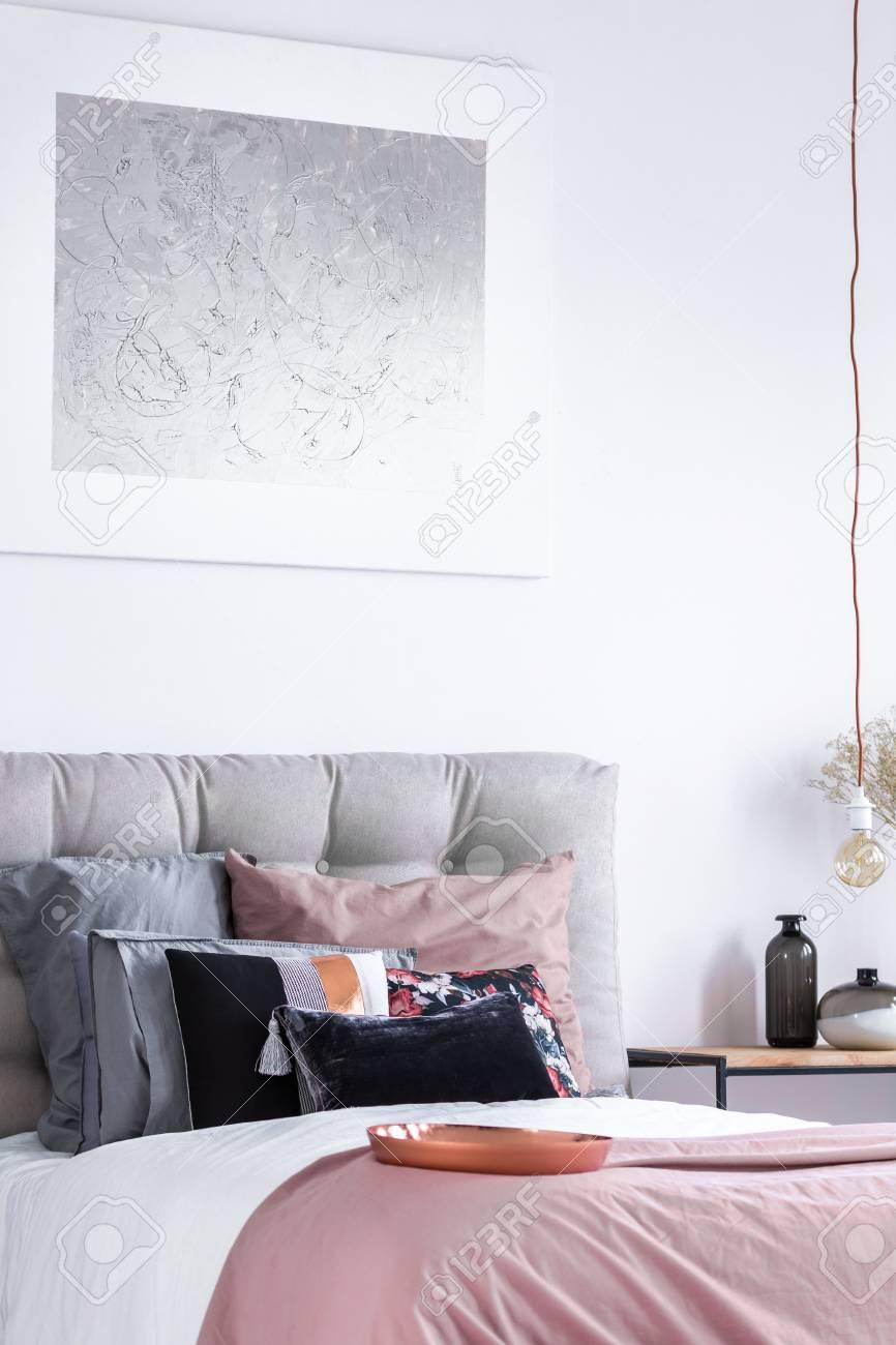Attraktiv Silbernes Gemälde über Kingsize Bett Mit Gemusterten Kissen Auf Rosa  Steppdecke Und Grauem Kopfteil Standard
