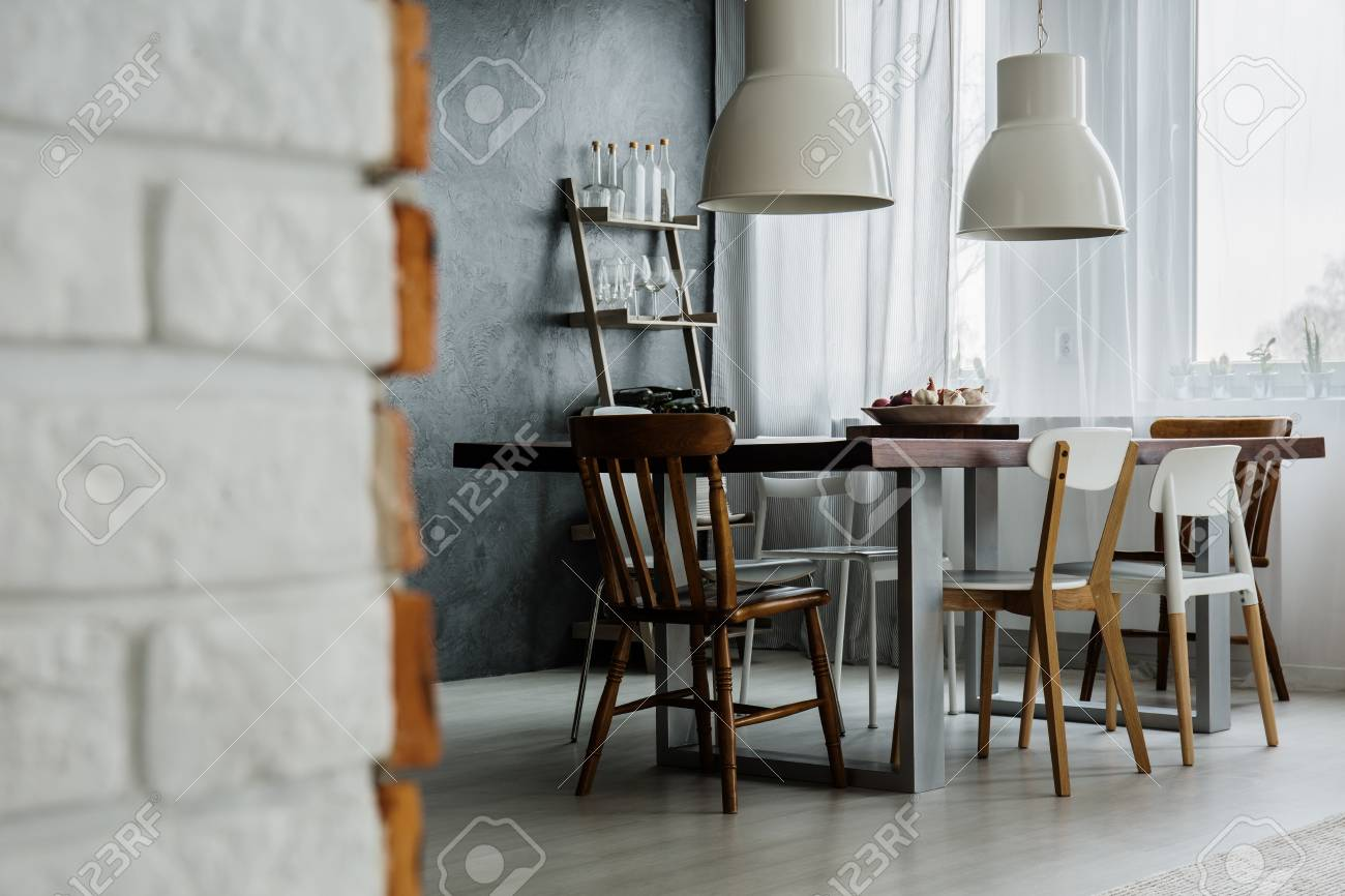 Chic dining room design with concrete wall and industrial chairs stock photo 85134309