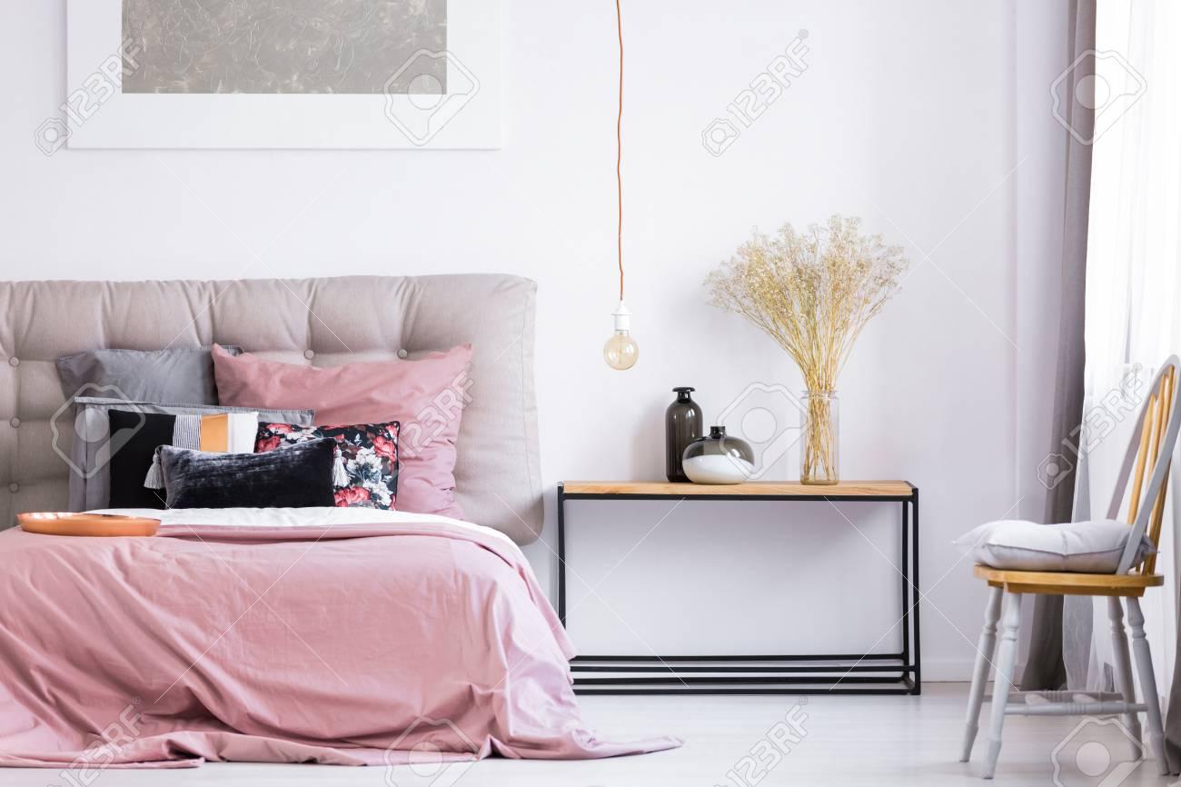 Oreiller gris sur chaise orange en fenêtre dans une chambre moderne avec  literie rose sur lit king-size