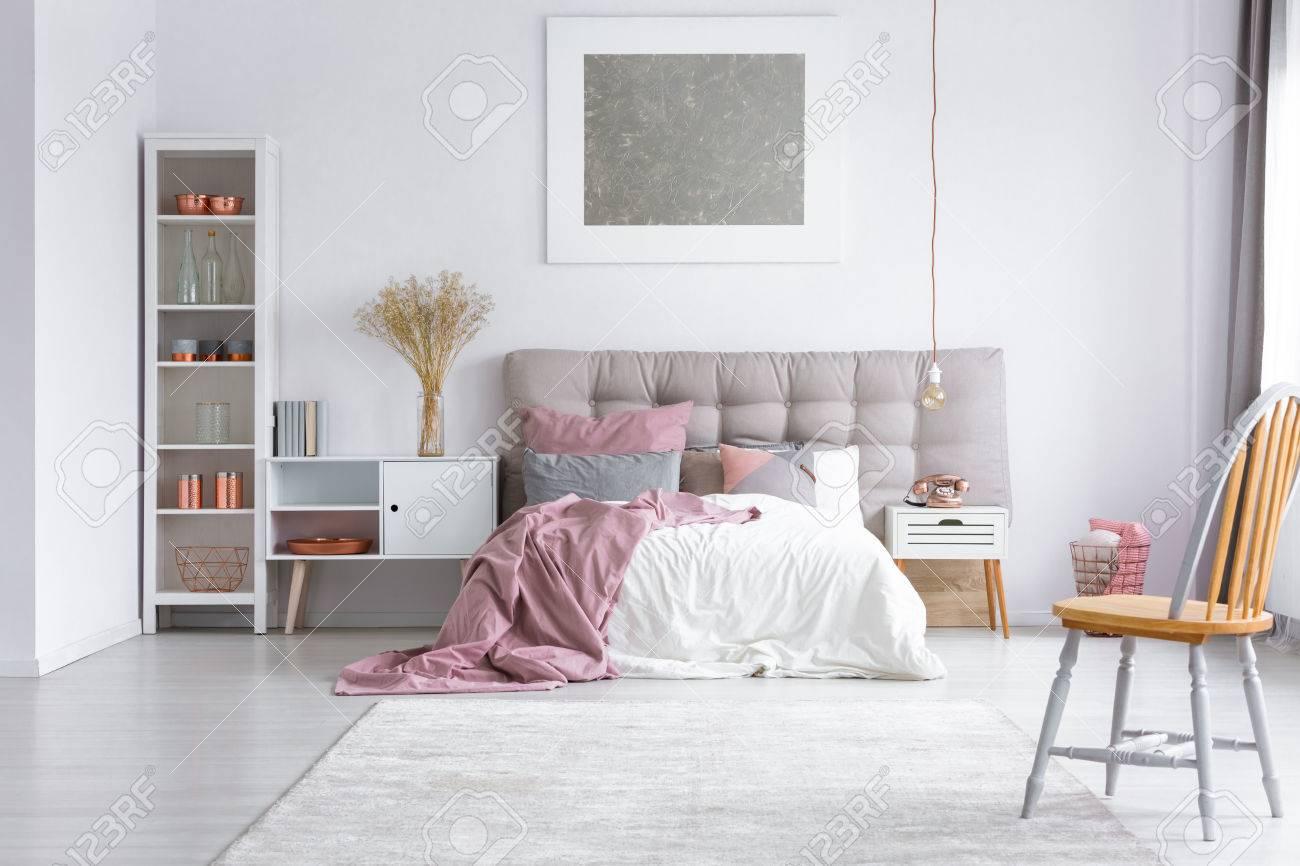 Orange Stuhl Auf Grauem Teppich Im Hellen Schlafzimmer Mit Silberner Malerei  über Kingsize Bett Und