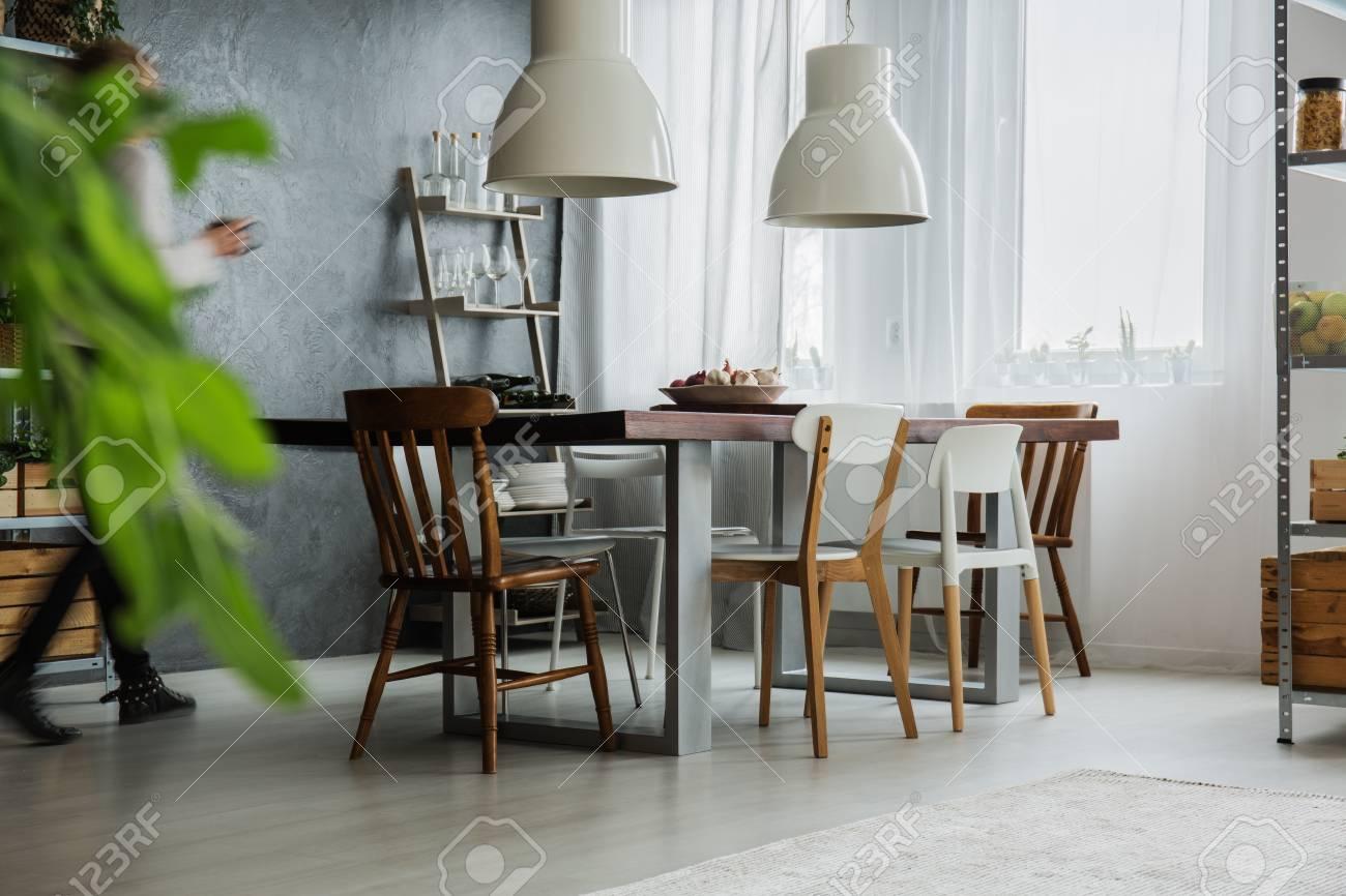 Rustikaler Tisch Verschiedene Stuhle Und Dunkle Wand Im Esszimmer Lizenzfreie Fotos Bilder Und Stock Fotografie Image 85134347