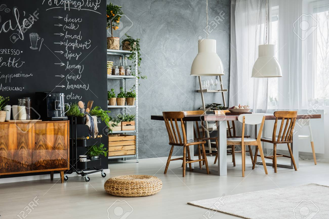 Trendy apartment with storage rack, dining set and chalkboard..