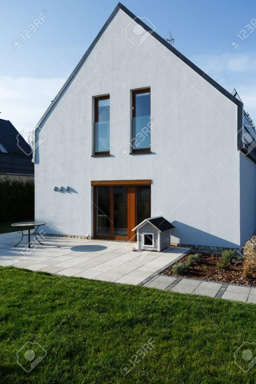 Extérieur de la maison moderne avec porte de terrasse en bois et pelouse  verte