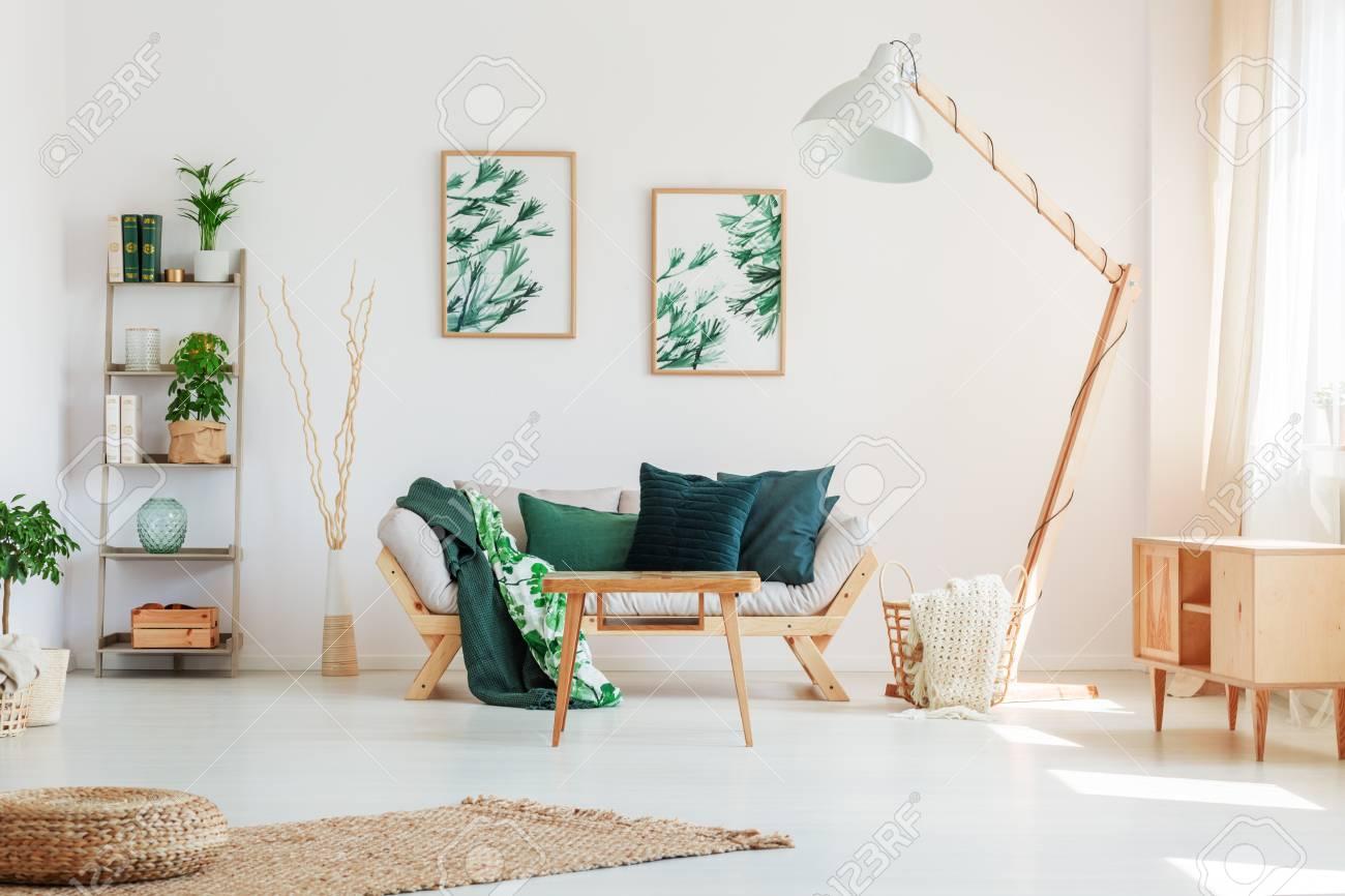 Oreiller Vert Foncé Sur Canapé Beige Contre Mur Blanc Avec Des Peintures Avec Motif Floral Dans Le Salon Naturel
