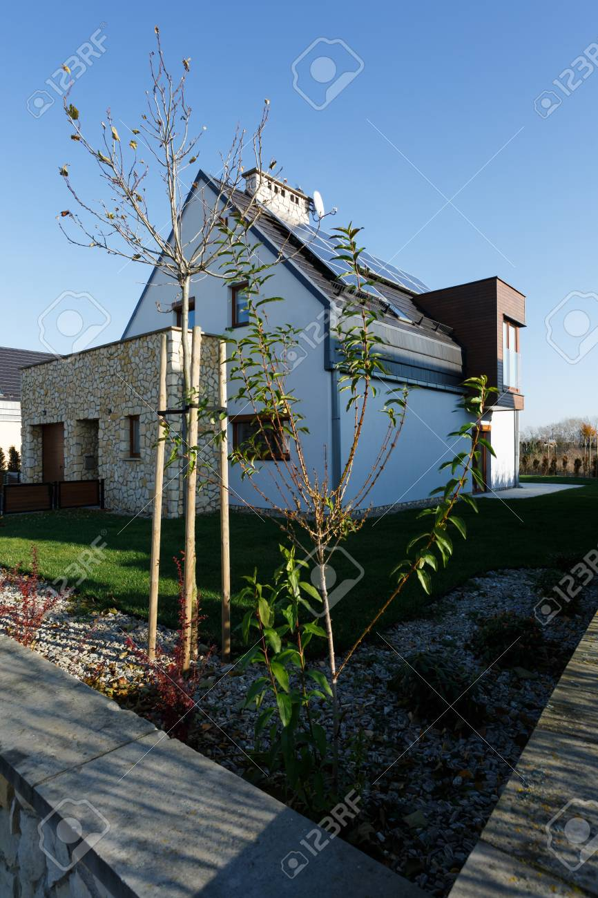 big modern house with brick exterior garden and solar panels stock