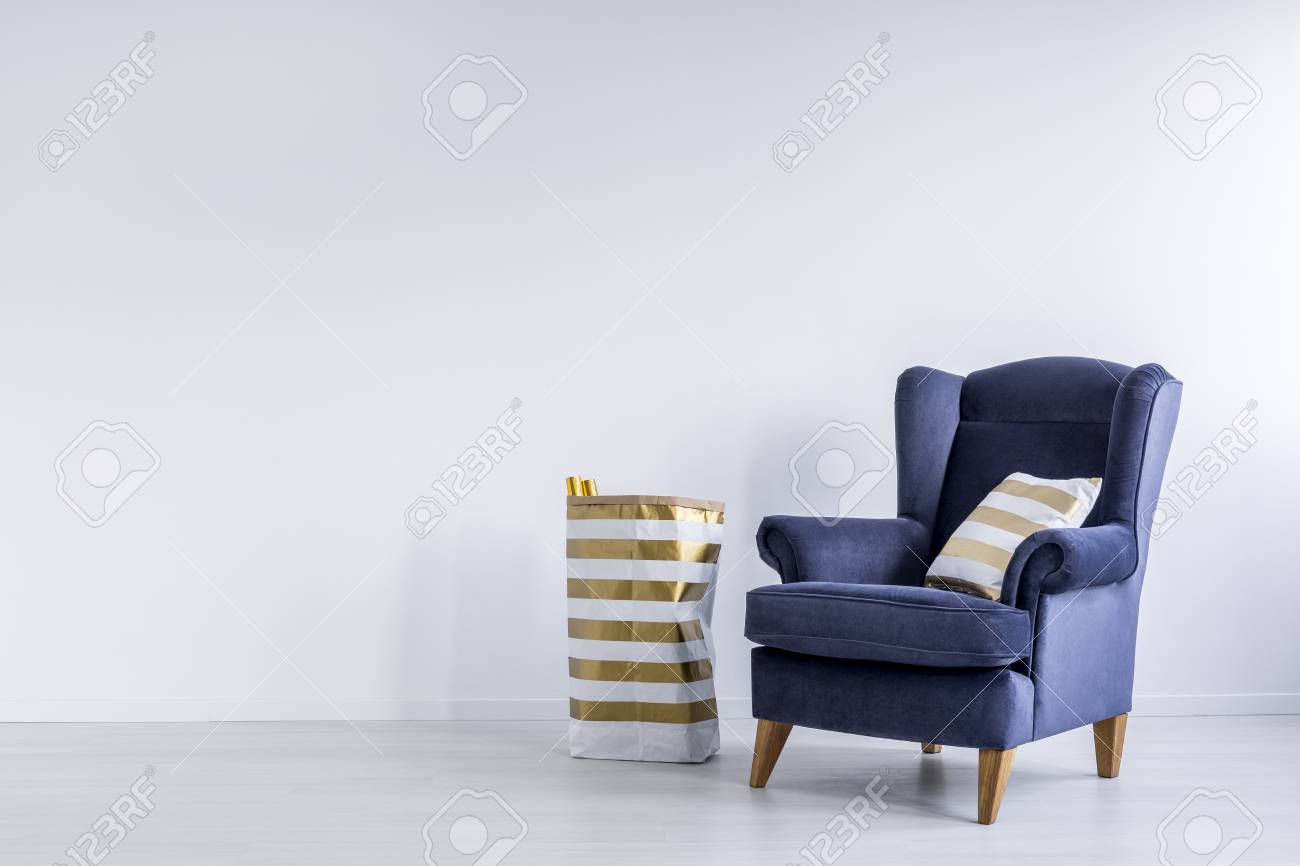 Striped Gold Pillow On Dark Blue Armchair And Pattern Paper Bag ...