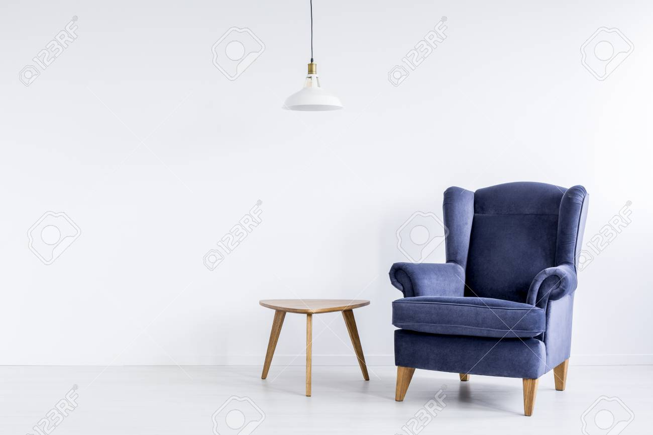 White lamp above wooden table next to dark blue classic armchair white lamp above wooden table next to dark blue classic armchair in spacious white room stock aloadofball Images