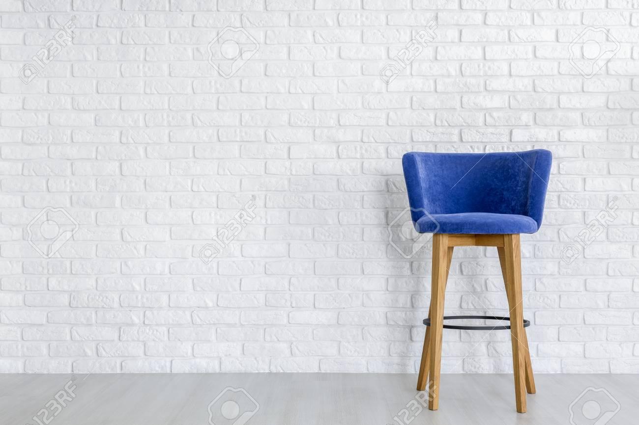 Sgabello da bar elegante blu navy con gambe in legno contro il