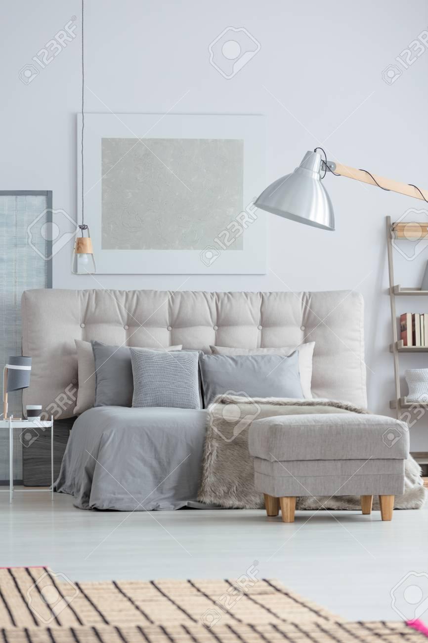 Interno moderno della camera da letto con comodo letto e tappeto di bambù  sul pavimento