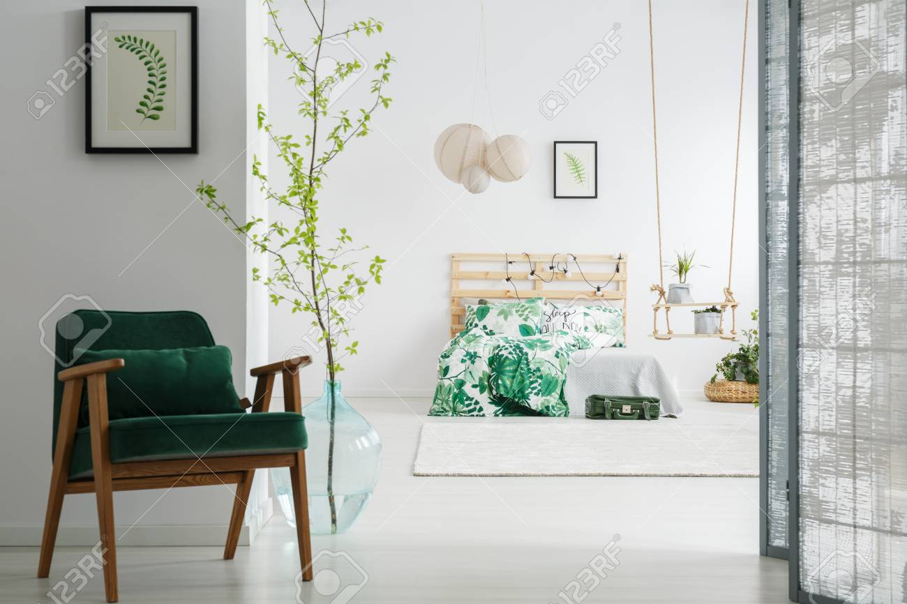 Dark green vintage chair in cozy bedroom with screen and tree..