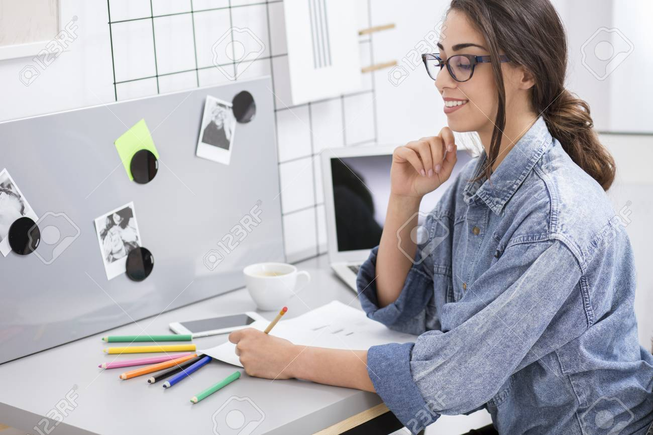 home office colorful girl. Pretty Girl Drawing Clothes Designs While Sitting At Desk With Smartphone And Colorful Pencils In Home Office A