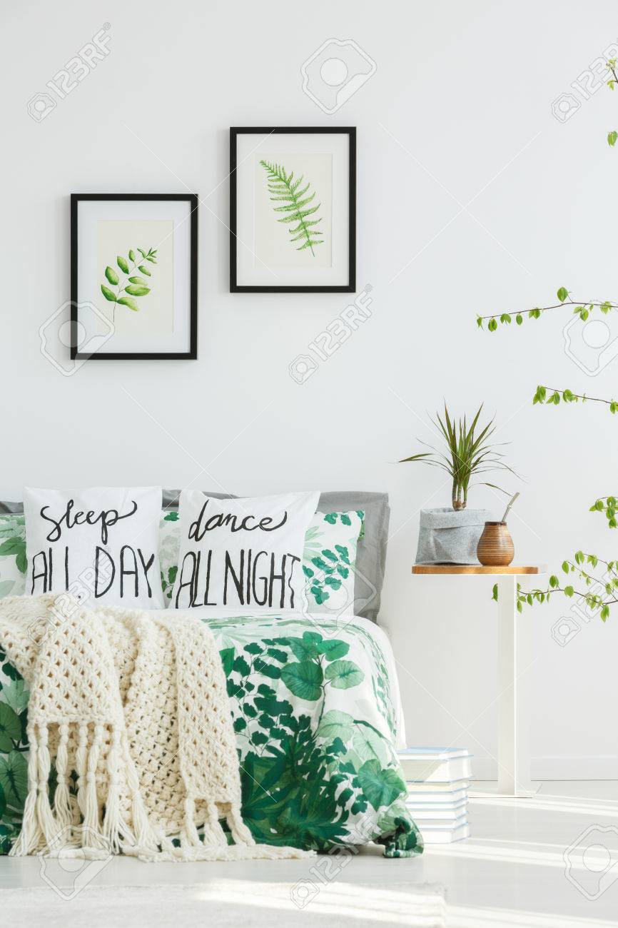 Leaves Paintings On White Wall Above Bed With Beige Knit Blanket