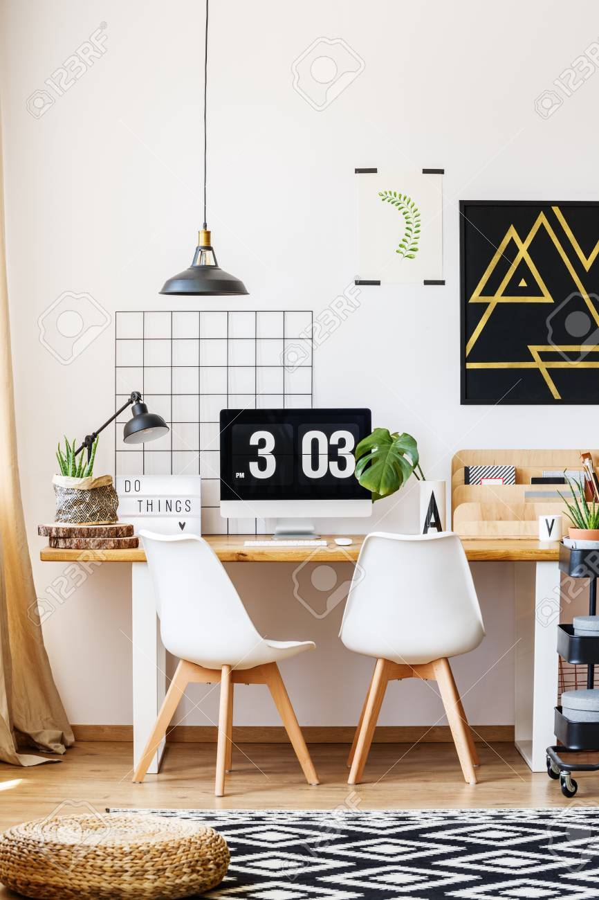 Stock Photo   Two White Designer Chairs And Wooden Desk In Cozy Room With  Contemporary Decor, Monstera Plant, Poster, Computer And Hipster Accessories