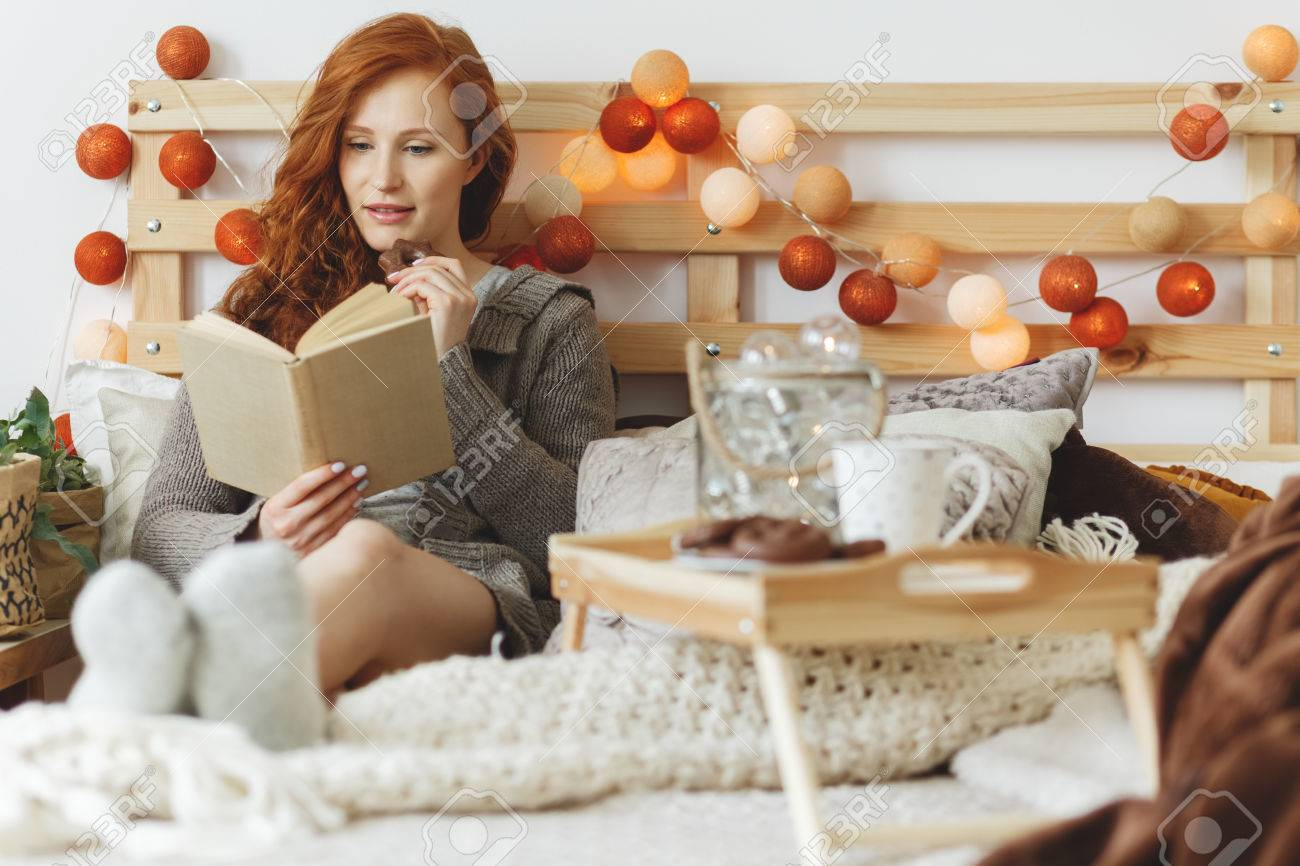Young woman eating chocolate gingerbread cookies while reading a book - 85281213
