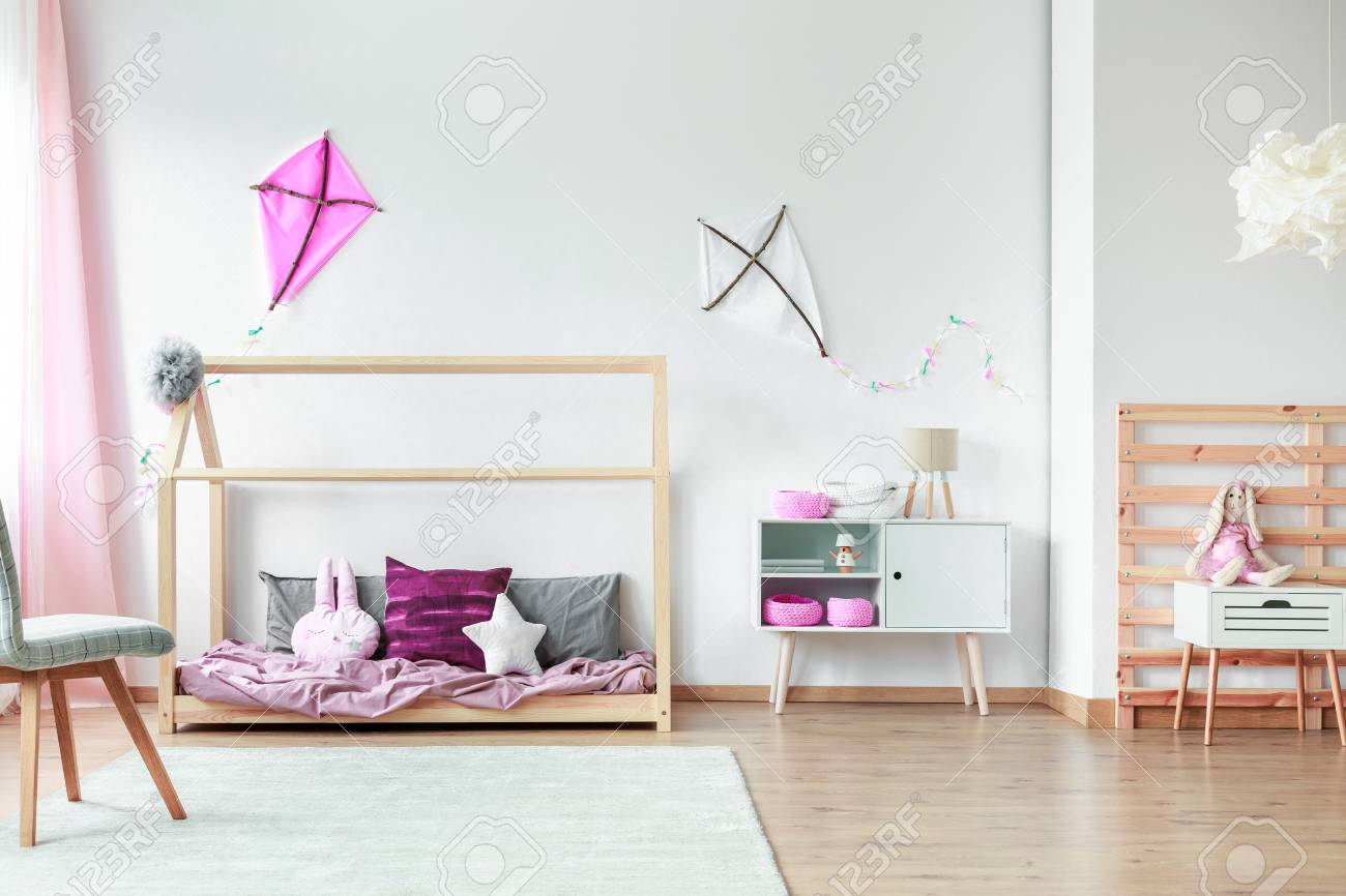 White and pink kite on wall in spacious kids bedroom with chair..