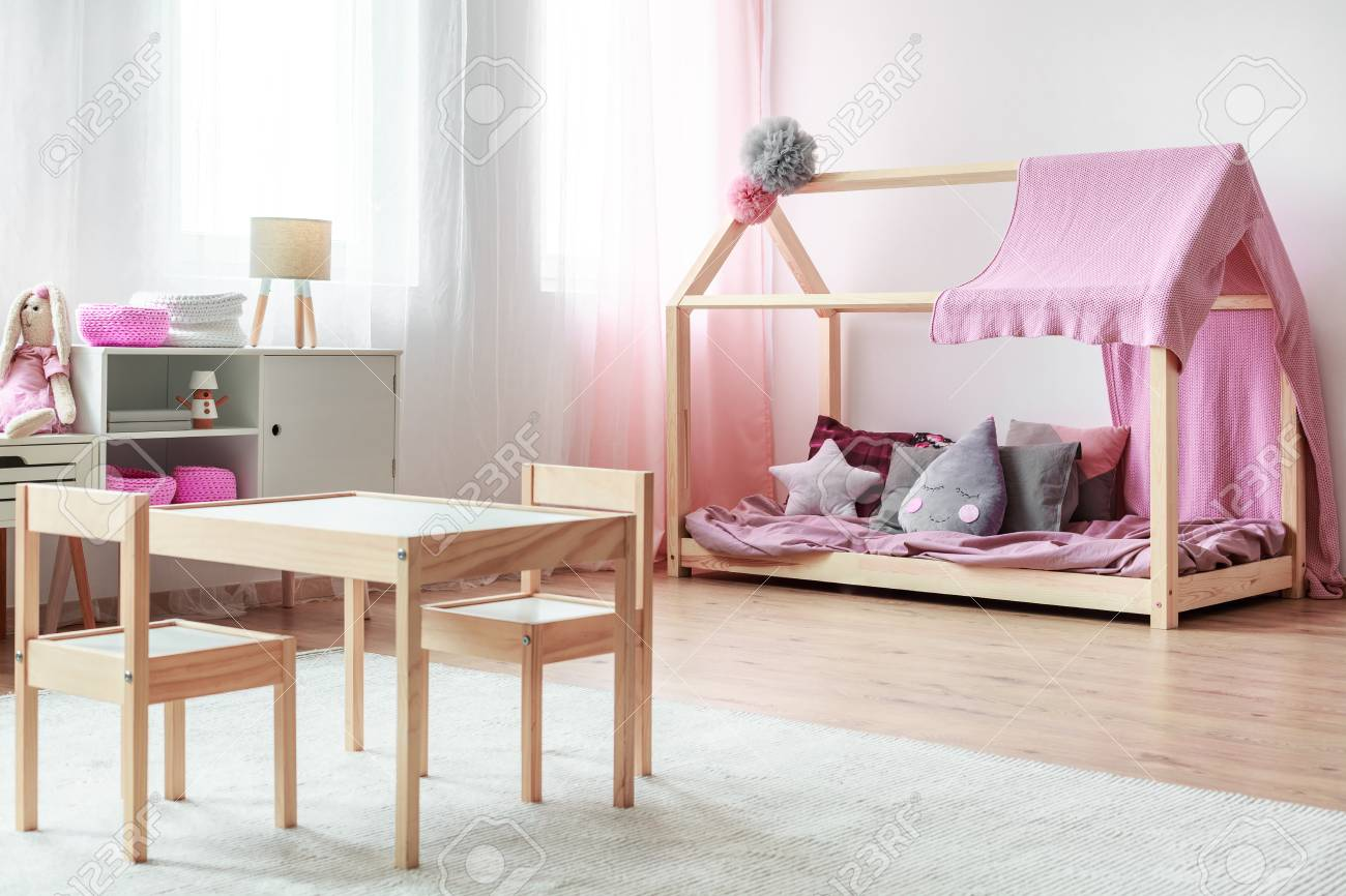 Kid\'s table and small chairs on white carpet in scandinavian..