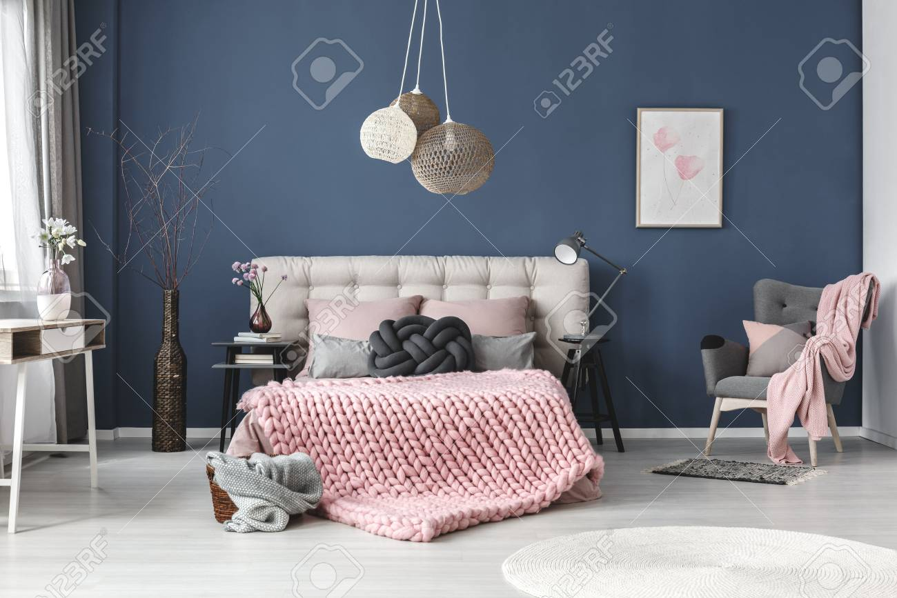 Grey Armchair With Pink Blanket And Pastel Pillow In Bedroom Subtle Painting On Blue Wall